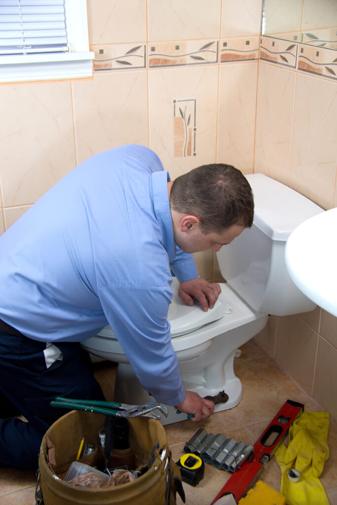 toilet plumber repairing commode in Stuart Florida