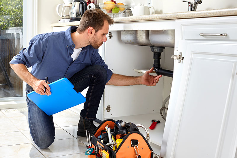 A plumber performs kitchen sink repairs in Stuart, Florida.